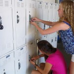 Sophomore Shae Langely reaches over her locker neighbor Danielle Gantar in this photo illustration. Encounters with locker-neighbors directly above or below may be awkward, but take notice of their presence and create room for them. No one wants to have to do the bend-and-reach.