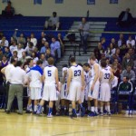 The DHS men's varsity basketball team surrounds their coach, Dan Gonzalez, during a second-quarter timeout on Break the Record Night, Feb. 1. Despite an early lead for the Laguna Creek Cardinals, the Devils won the game 86-80.