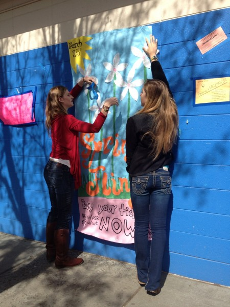 Kylie Dunn and Lara Vanderbilt put up a Spring Fling poster. The dance will begin after the men's lacrosse game on March 15.