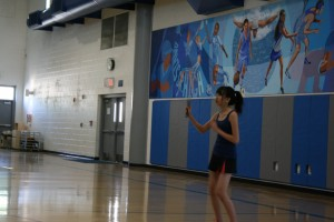 2.Junior Zhongxia Yan warms up with the rest of the DHS badminton team. Yan played in exhibition matches during the 4/12 game.