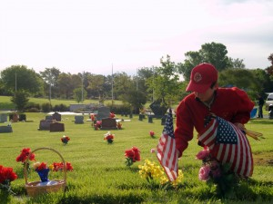 Kyle Powell honors a veteran by planting a flag on a grave.