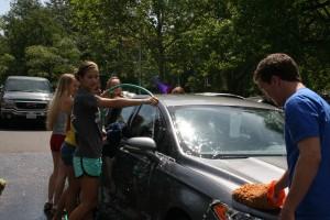 Student Gov members scrub hard to clean a teachers car