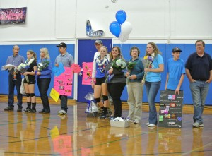(From left to right) Davis varsity volleyball seniors Mackenzie Harrison, Zoe Hunt-Murray and Jen Blanc stand with their families holding the gifts they have received from JV players and fellow varsity teammates during Senior Night in the South Gym on Nov. 5. They are playing against Elk Grove.