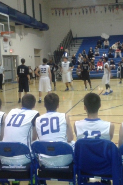 Players on the JV men's basketball team watch one of their teammates attempt a  free throw.