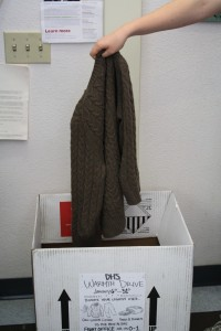 A student donates a sweater to the Sexual Assault and Domestic Violence Center through the Feminism Club donation box in room 0-4. (Photo Illustration)