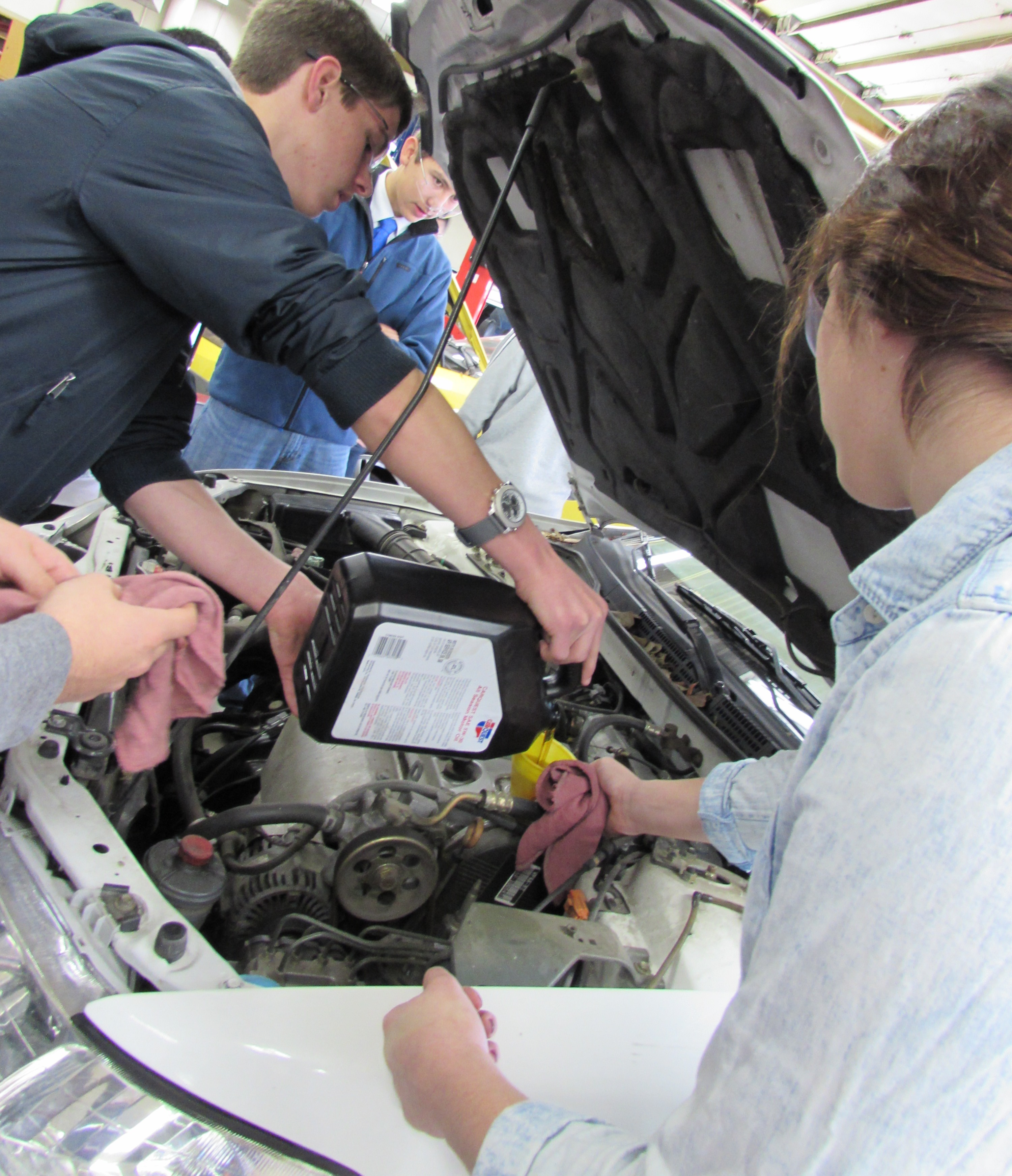 Students in Robert Thayer's second period Basic Auto class change the oil in a shop car. Photo by Chloe Sommer