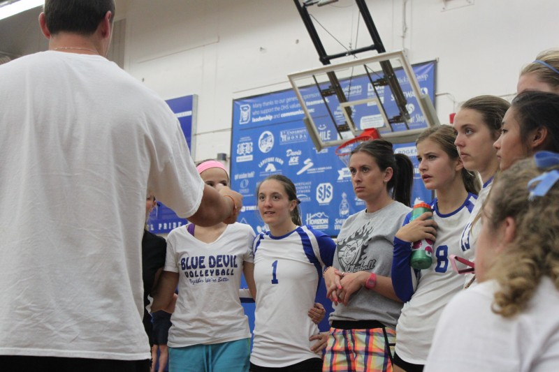 Coach Julie Crawford and the women's varsity volleyball team huddles during a timeout.
