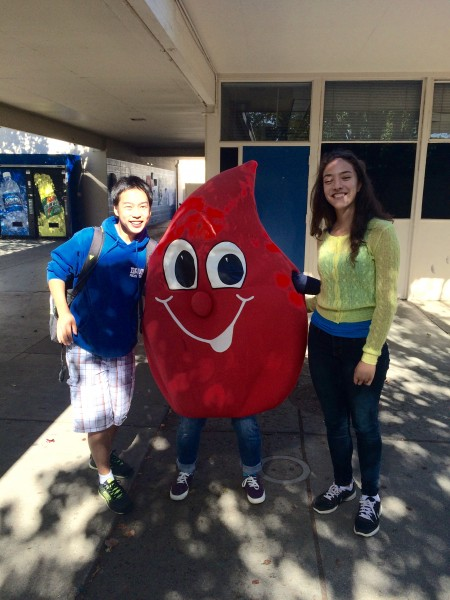DHS sophomore and Red Cross Club member Ivy Zhou is dressed up as a drop of blood in order to encourage students to donate blood during the blood drive. Sophomores Jeffrey Zhang (left) and Emily Koschar (right) pose with Zhou.