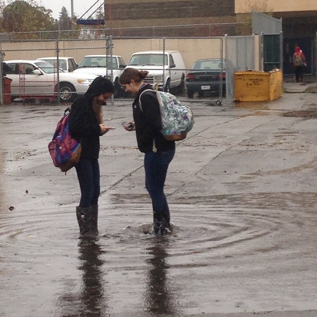 While most students hid from the storm in dry classrooms and some didn't come to school at all , sophomores Mariana Puente and Maddie English decided to chat in the middle of the biggest puddle on campus. (Photo: D. Newman)