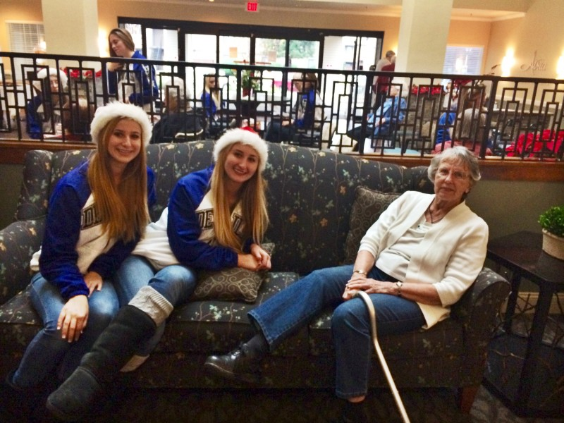 Elaina Hupe and Lauren Hupe socializing with a resident from Atria.