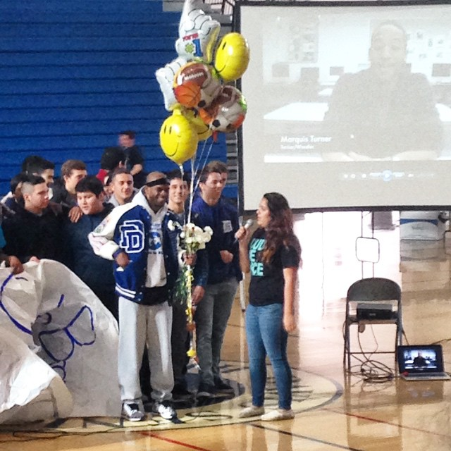 LEAD member Estephanie Franco presents the person of honor, Ty  Brown at the 'Dude Be Nice' assembly during lunch. Brown coaches football and wrestling, and for his kindness and inspiration, the LEAD class gave him tickets to the Grizzlies vs. Kings game (and free babysitting). (Photo: D. Newman)