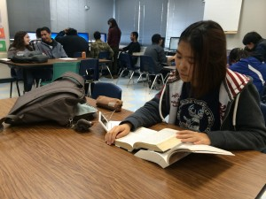 Junior English Learner Hyejun Hong studies for her American Literature class using her electronic translator and a Korean and English version of the book The Grapes of Wrath by John Steinbeck.