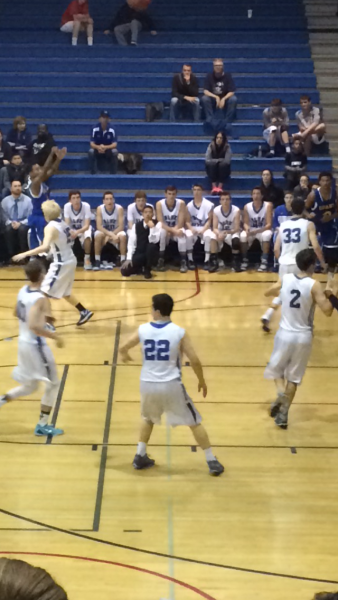 The men's varsity basketball team gets set in a zone defense against Grant. They won the game 81-78.