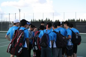 The Blue Devils gather around senior Louis Pak. Pak led the cheer before players dispersed and headed to their separated matches.