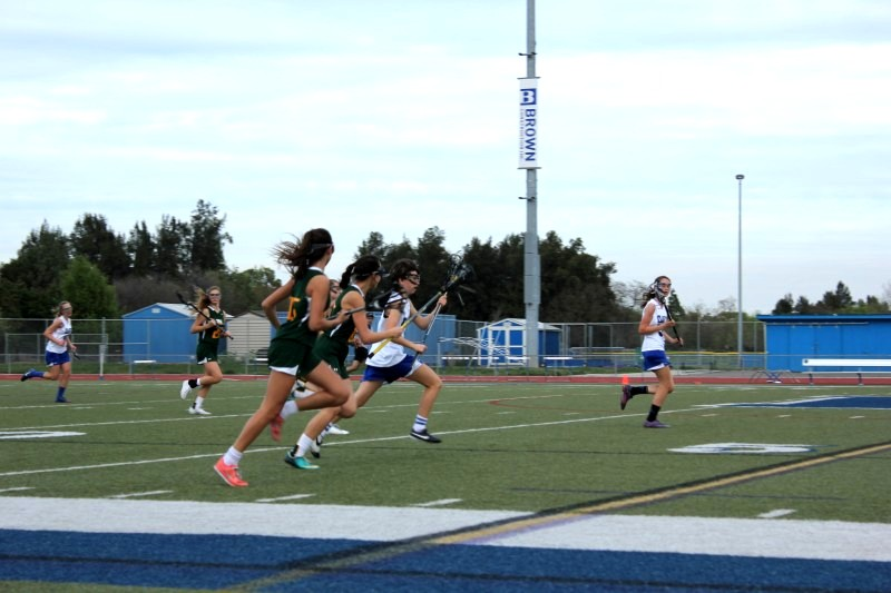 Sophomore Lucy Shauman #7 makes a run with the ball while teammate Addie O'Hanlon #18 waits for the pass