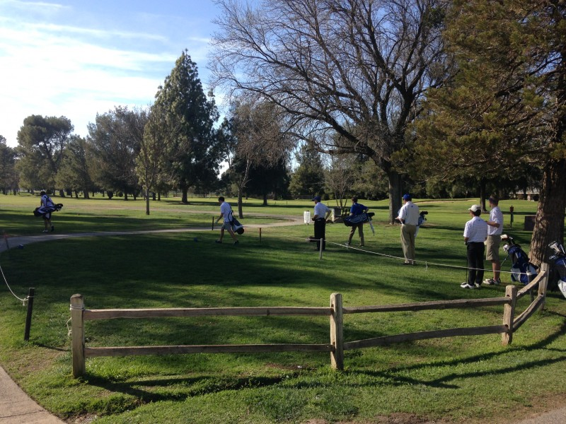The JV men's golf team tees off as the match begins, leading with Dylan Lee and Daniel Shuman.