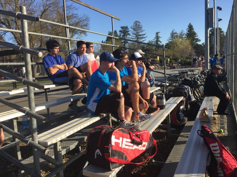 Members of the men's varsity tennis team attentively watch their teammates in Wednesday's match against Jesuit.
