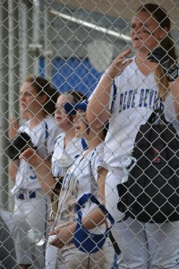 Lady Devils cheer from the dugout while their fellow player are up at bat. .jpg