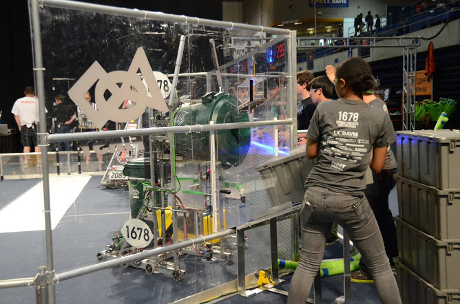 Yamoah gives a tote to the robot at the Sacramento Regional earlier this season. Courtesy photo by Ben Hoffner-Brodsky.