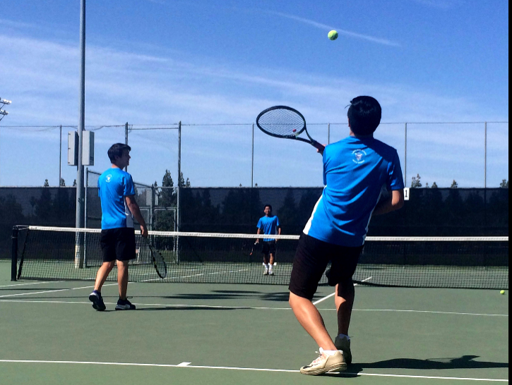 Junior Nathan Dao warms up with his teammates before the match against Franklin. Dao won his doubles match 6-1 and 6-0.