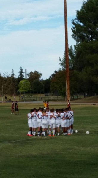 The men's varsity soccer team huddles up before their 7-0 win over Vintage High School.