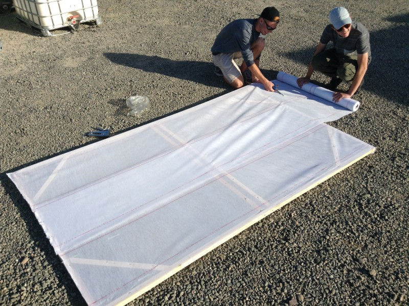 Seniors Eric Smith and Daniel Johnson stretch a drop cloth across a wooden frame as part of senior float construction.