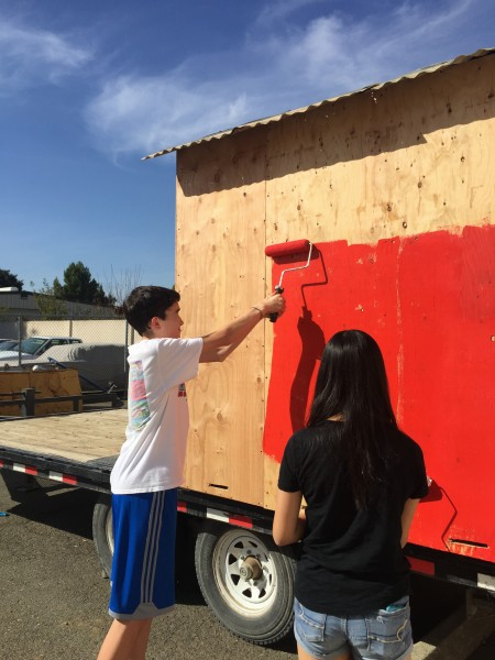 Sophomores Grayson McKim and Jun Kim help paint float along with other volunteers
