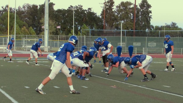 The Davis High varsity football team sets up a play during preseason practice. The Devils will face the Sheldon Huskies on the Oct. 9 homecoming game.