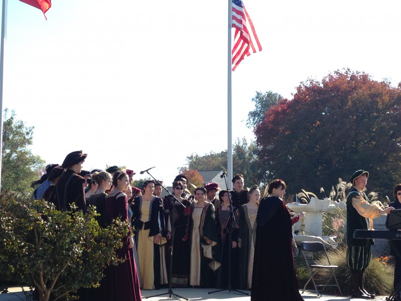 The Madrigals stand in front of the audience, ready to perform.