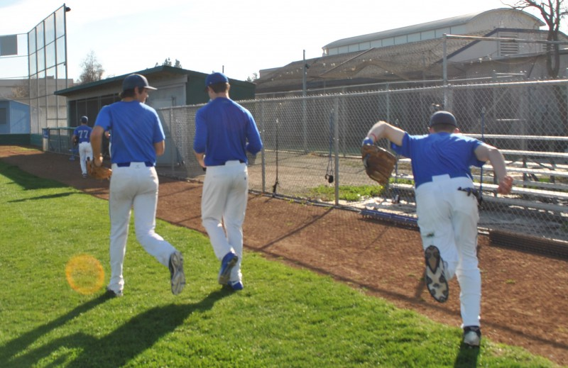 Baseball players Daniel Henrickson, Ryan Holgate, and Tyler Mortenson run to the dugout to discuss the practice schedule with their coach.