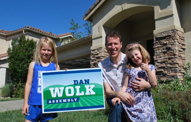 Dan Wolk, a 1995 alumnus of Davis High, poses in front of his state assembly sign with his two daughters.