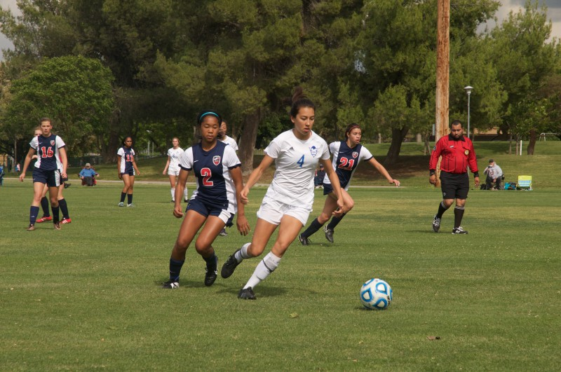 Junior Sidra Bugsch dribbles the ball away from a defender. The Devils won 7-1.