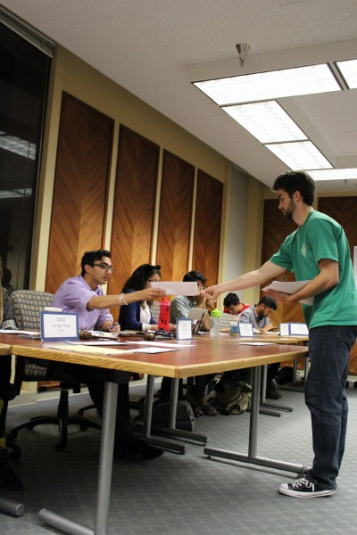 Harley Litzelman hands out copies of the resolution to ASUCD senators. (K. Sturm)