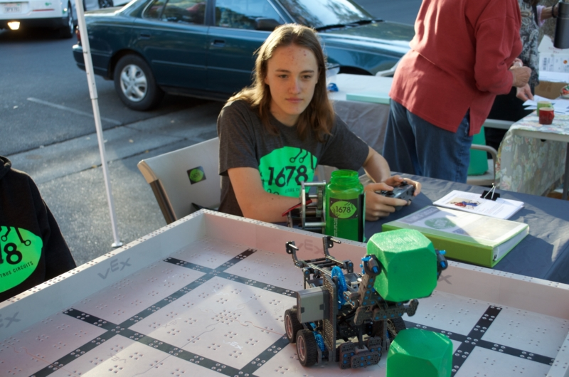 Junior Finn O'toole Boire stacks blocks via the Citrus Circuit's handcrafted robot to attract people to their booth at the Davis Farmers Market. The Farmers Market outreach team promotes their team every Saturday and Wednesday.