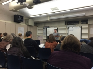 """Parents take their seats, listening to """"The Compassion Project's"""" first meeting."""