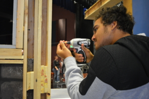 Senior Rodrik Davis puts together sets during stagecraft to prepare for the play during tech week.