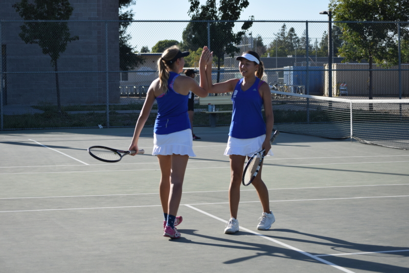 Seniors Chiara Armstrong and Amy Fang share a high five during doubles. (Photo: L. Jelks)