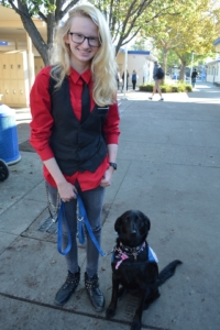 Junior Skye McIlraith poses with her service dog Olive.