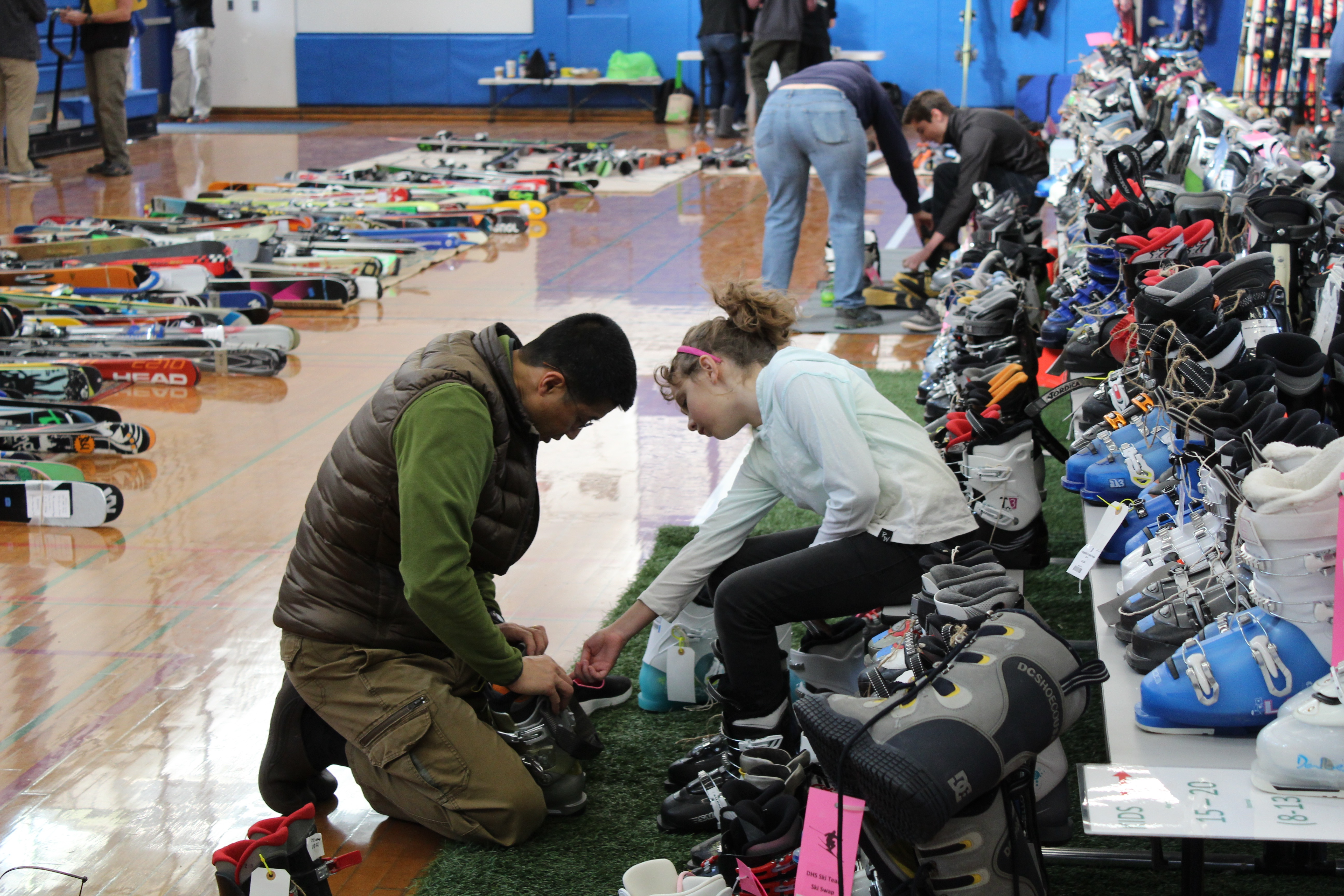 Volunteer parents help out customers with trying on boots and skis.