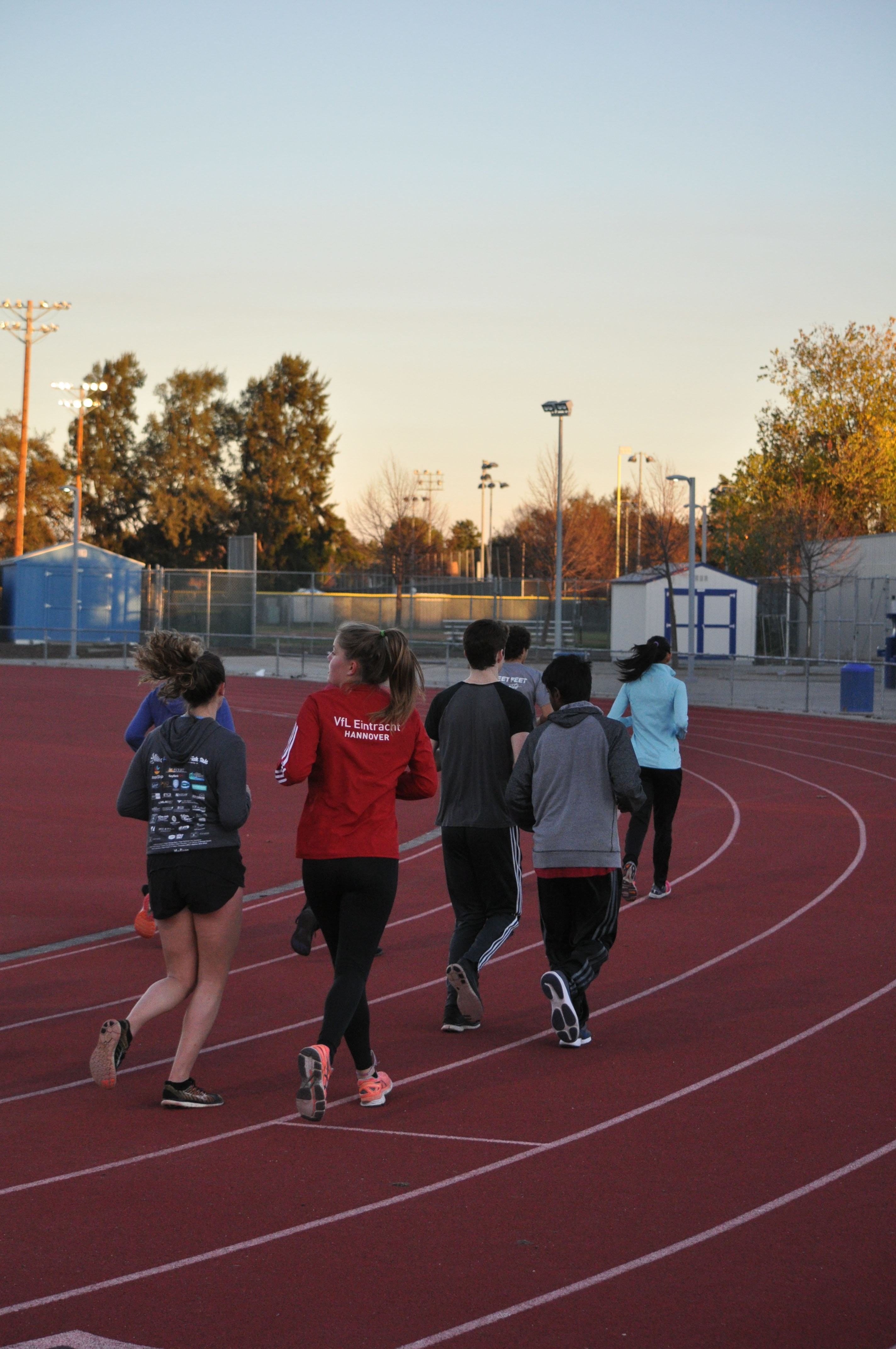 A group of runners begins a lap around the track.