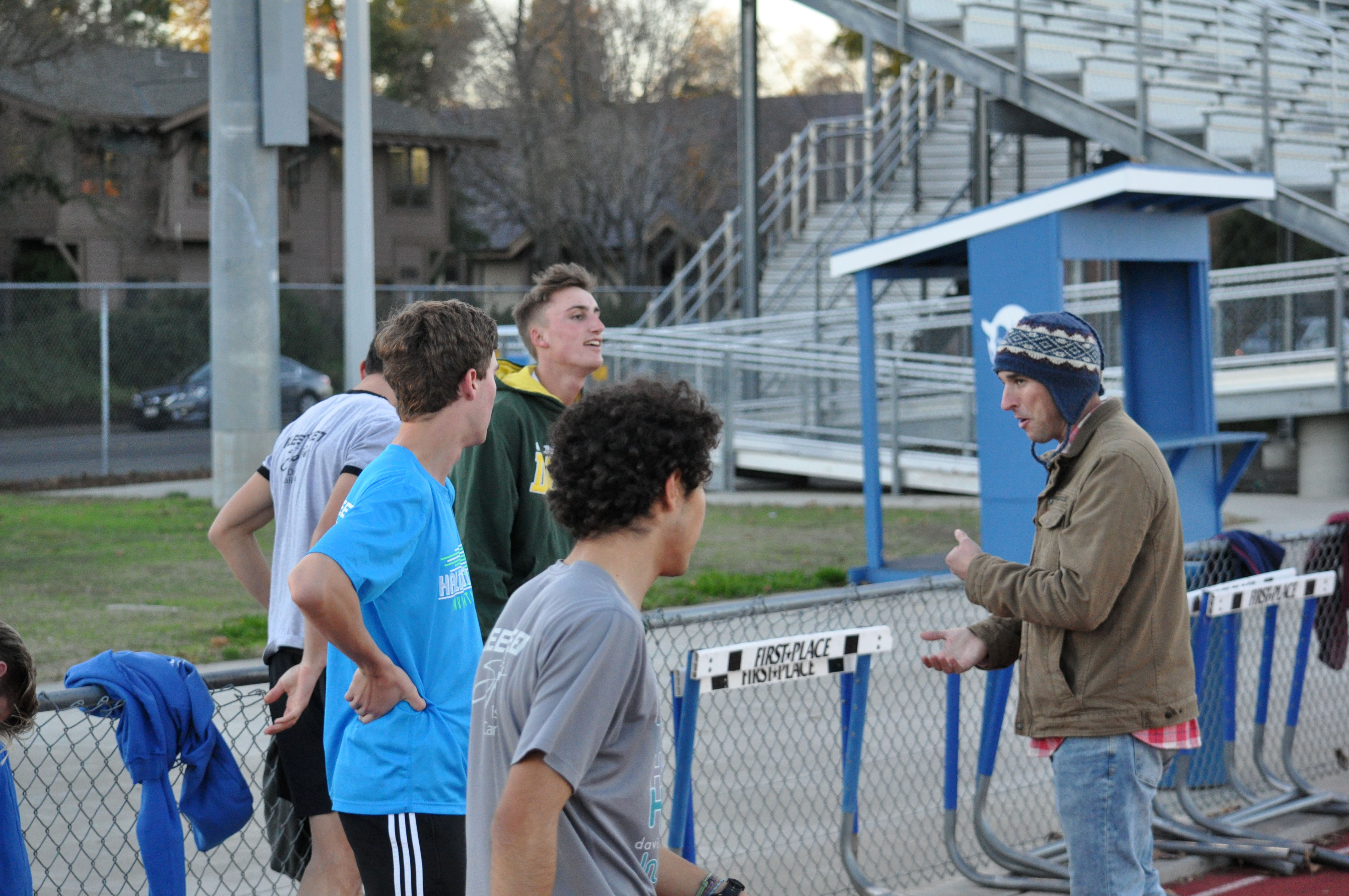 Head coach Spencer Elliott talks with runners during a break at practice.