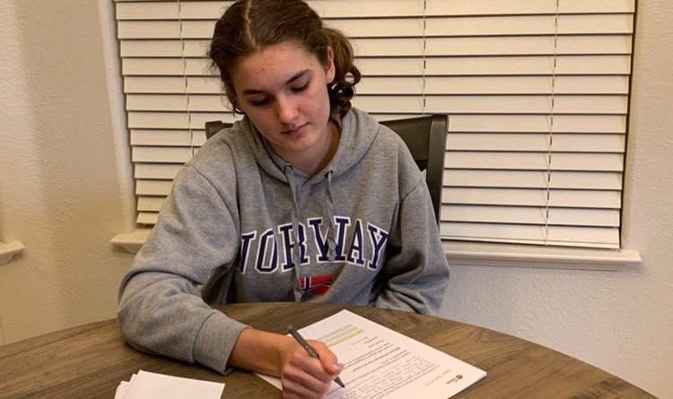 Senior Emma Carney is sitting at a table in her house writing a letter for Vote Forward.