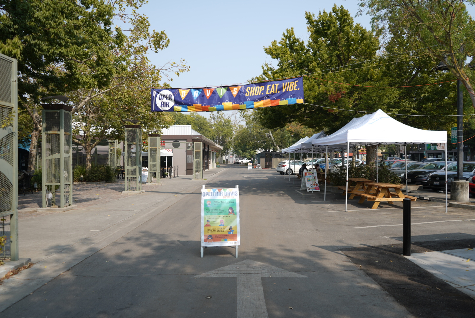 "A sign stands under a banner signifying the ""open-air"" part of downtown Davis."
