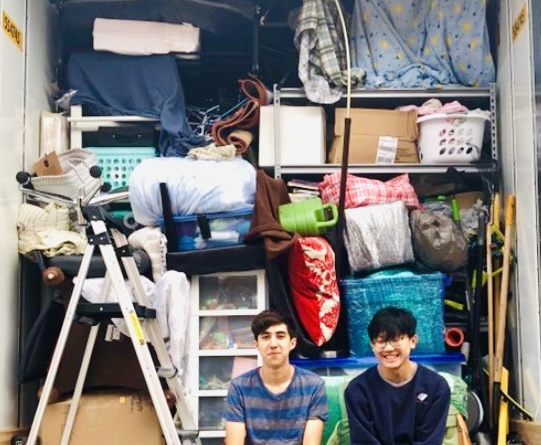 George Zhou and his friend Caleb Davis sit in the bottom right corner of Zhou's open moving van with all his belongings behind them