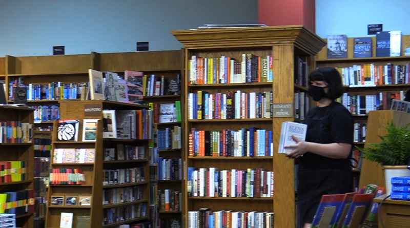Books fill the shelves inside the Avid Reader bookstore. A customer wearing a mask stands on the right holding a book