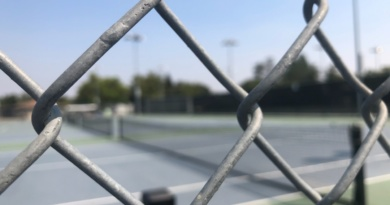 Through the fence, the Davis High tennis courts remain empty
