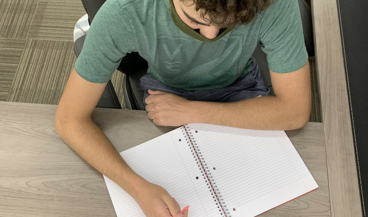 Davis High alumnus Robbie Silver holding a pencil above his notebook, preparing to take notes for his online class.