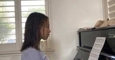 Emily Jiang sits at a piano, posed to play.