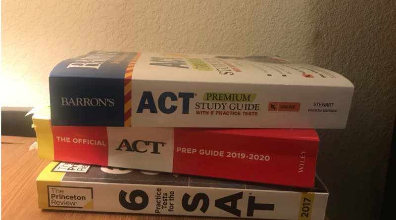 Three workbooks stacked on a desk: the Barron's ACT premium study guide, The Official ACT Prep Guide 2019-20 and the Princeton Review SAT 2017