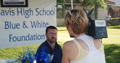 "Will Arnold being interviewed by a person holding a camera. The sign behind him reads ""Davis High School Blue & White Foundation"""